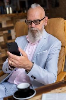 Porträt des stilvollen älteren mannes, der auf seinem telefon schaut