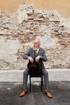 Porträt des stilvollen älteren mannes, der draußen sitzt