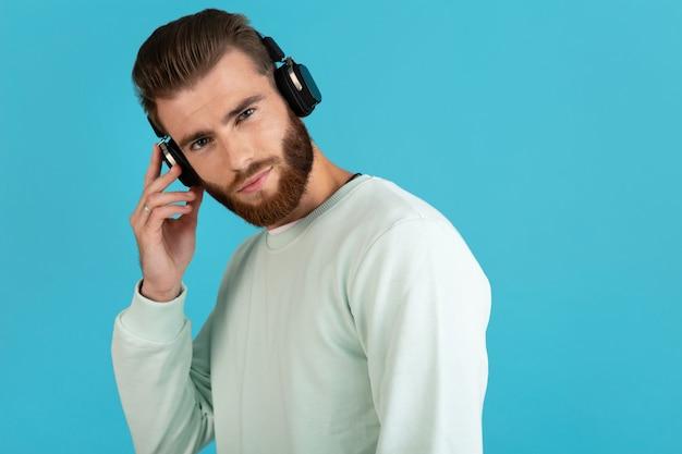 Porträt des stilvollen attraktiven jungen bärtigen mannes, der musik auf drahtlosen kopfhörern des modernen stils selbstbewusster stimmung lokalisiert auf blauem hintergrund hört