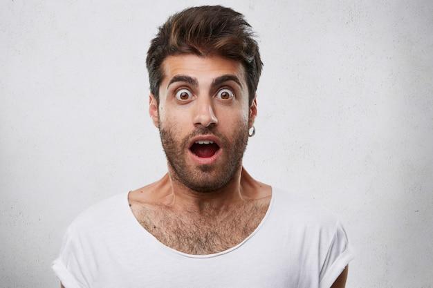 Porträt des stilvollen bärtigen kerls mit der trendigen frisur, die ohrring und weißes t-shirt trägt, das mit seinen augen schaut, sprang heraus und öffnete mund, der schock und ängstlichen blick hat.