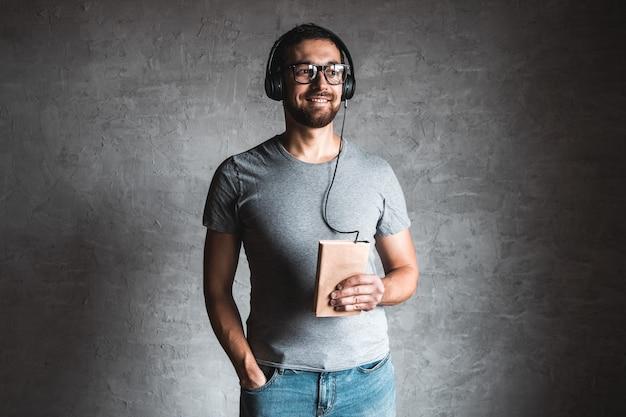 Porträt des stilvollen bärtigen mannes gekleidet im grauen lässigen t-shirt, das hörbuch mit seinen kopfhörern und auf grau hört