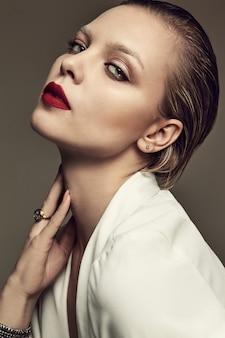 Porträt des stilvollen brünetten frauenmodells der schönen mode mit abendmake-up und roten lippen in weißer jacke