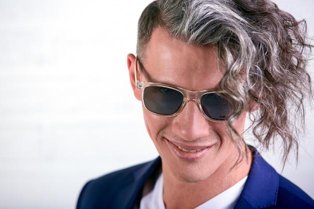 Porträt des stilvollen geschäftsmannes mit dem lockigen langen haar in der sonnenbrille, die an der kamera auf weißer wand lächelt