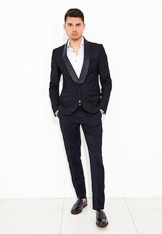 Porträt des stilvollen geschäftsmannmodells der hübschen mode kleidete in der eleganten schwarzen klassischen anzugsaufstellung an. metrosexuell