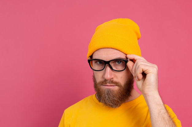 Porträt des stilvollen hübschen europäischen bärtigen mannes im lässigen gelben hemdhut und in den gläsern auf rosa