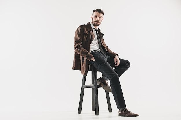 Porträt des stilvollen hübschen jungen mannes, der gegen weiß sitzt. mann trägt jacke