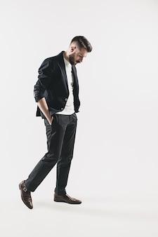 Porträt des stilvollen hübschen jungen mannes, der gegen weiß steht. mann trägt jacke
