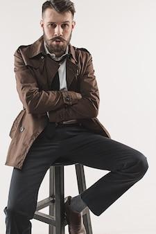 Porträt des stilvollen hübschen jungen mannes, der im studio gegen weiß sitzt. mann trägt jacke
