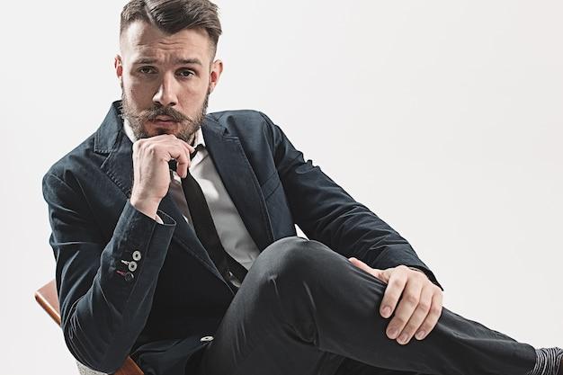 Porträt des stilvollen hübschen jungen mannes, der im studio gegen weiß sitzt.
