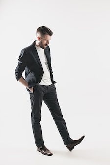 Porträt des stilvollen hübschen jungen mannes, der im studio gegen weiß steht. mann trägt jacke
