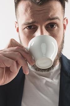 Porträt des stilvollen hübschen jungen mannes, der im studio steht. mann, der jacke trägt und tasse kaffee hält