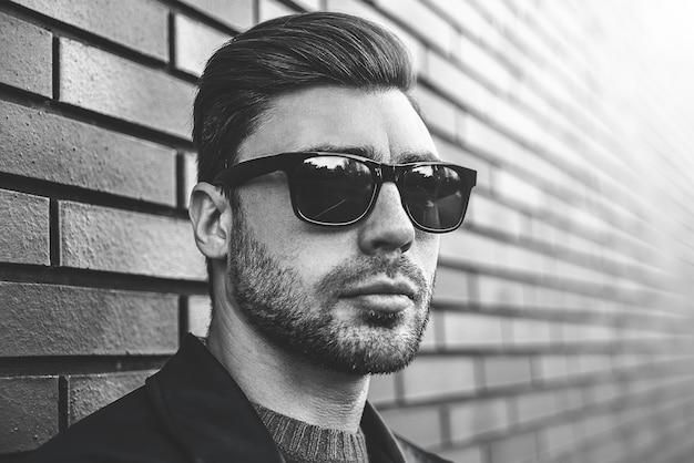 Porträt des stilvollen hübschen jungen mannes mit der borste, die draußen steht und sich auf backsteinmauer stützt. mann, der jacke, pullover und sonnenbrille trägt.