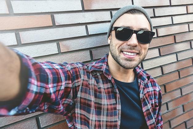 Porträt des stilvollen hübschen jungen mannes mit der borste, die draußen steht und sich auf backsteinmauer stützt. mann, der sonnenbrille und hut trägt. mann macht selfie.
