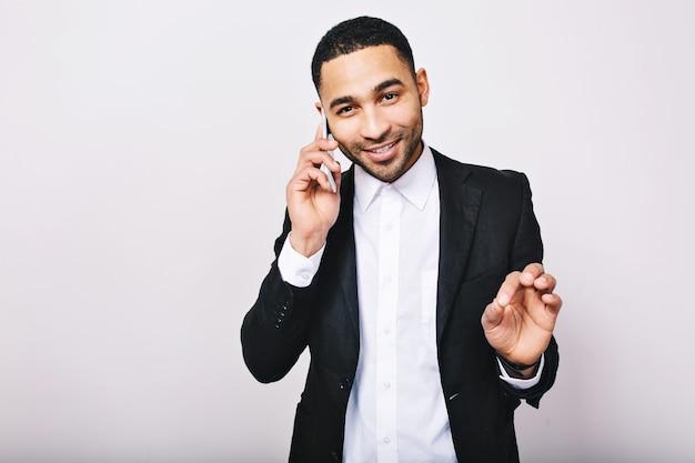 Porträt des stilvollen jungen gutaussehenden mannes im weißen hemd, in der schwarzen jacke, die am telefon spricht und lächelt. erfolg erzielen, echte positive emotionen ausdrücken, geschäftsmann.