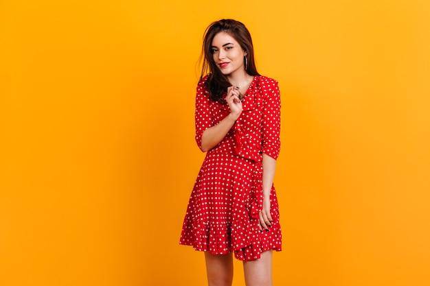 Porträt des stilvollen jungen mädchens im roten kleid. modell ist süß lächelnd auf orange wand.