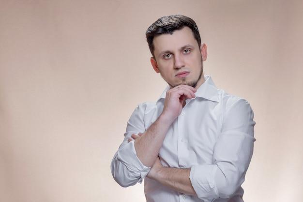 Porträt des stilvollen kaukasischen mannes auf braunem hintergrund. hübscher junger mann schaut in die kamera.
