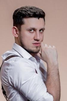 Porträt des stilvollen kaukasischen mannes lokalisiert auf braunem hintergrund. hübscher junger mann schaut in die kamera.