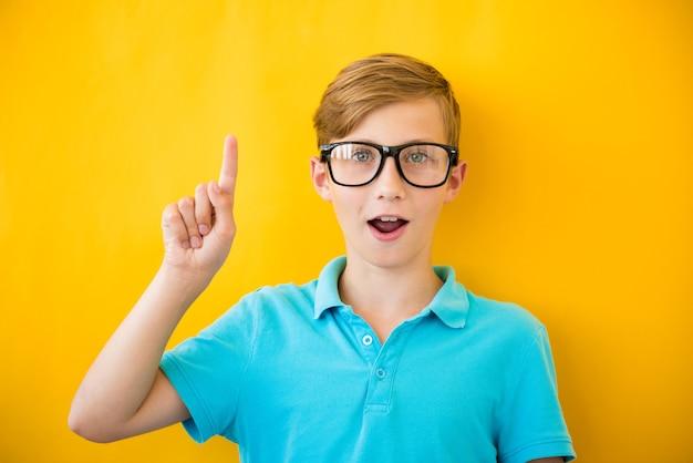 Porträt des stilvollen kleinen jungen mit dem finger nach oben. kind auf gelber tafel. erfolg, gute idee, kreative ideen und innovationstechnologiekonzept
