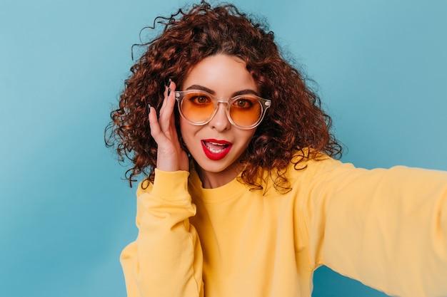 Porträt des stilvollen mädchens mit dem kurzen lockigen haar gekleidet im gelben pullover. mädchen in orange brille macht selfie auf blauem raum.