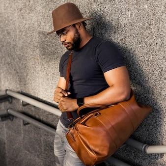 Porträt des stilvollen mannes, der eine tasche hält