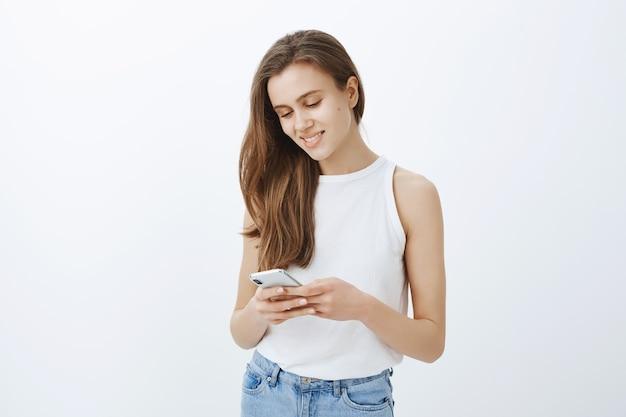 Porträt des stilvollen modernen jungen mädchens unter verwendung des smartphones und des glücklichen lächelns
