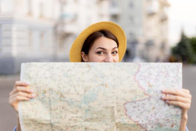 Porträt des stilvollen reisenden mit hut, das karte hält