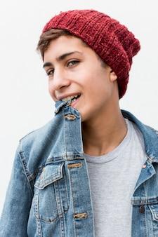 Porträt des stilvollen teenagers mit kragen des denimhemdes in seinem mund gegen weißen hintergrund