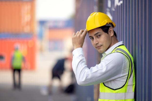 Porträt des stolzen ingenieurs in der arbeitsschutzkleidung, die in einem versandhof steht