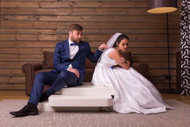 Porträt des streitfamilienpaares, das auf dem tisch auf holzraum sitzt