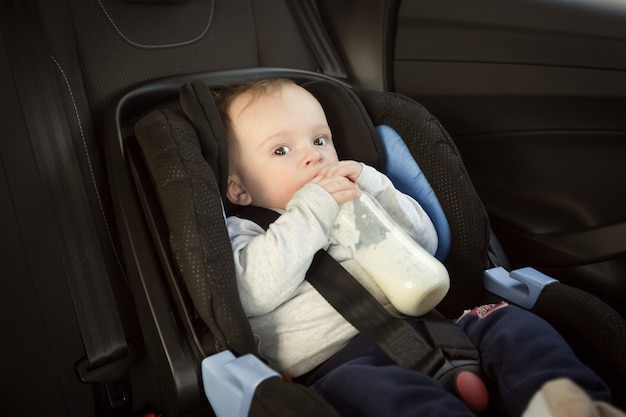 Porträt des süßen babys, das milch im autokindersitz trinkt