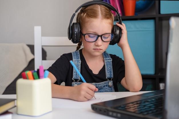 Porträt des süßen kaukasischen rothaarigen mädchens in brillen hören in der kopfhörerstunde im laptop, während sie zu hause studieren, fernbildungskonzept. hausaufgaben schreiben. quarantäne. zurück zum schulkonzept.