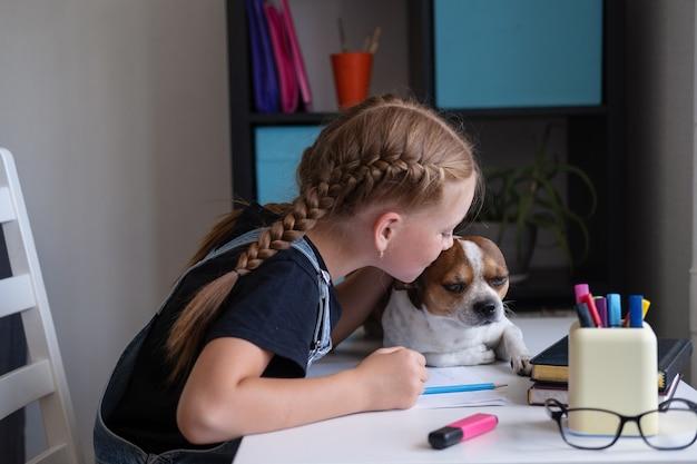 Porträt des süßen kaukasischen rothaarigenmädchens, das zu hause mit chihuahua-hund studiert, sitzt auf dem tisch, fernbildungskonzept. kind küssen den hund. hundehilfe bei den hausaufgaben. zurück zum schulkonzept.