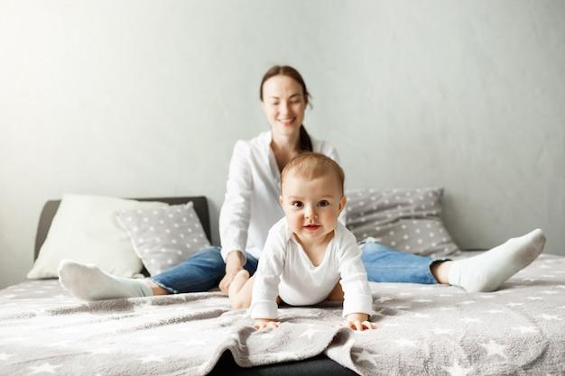 Porträt des süßen kleinen babys, das mit mutter auf bett sitzt und in kamerarichtung mit interessiertem und aufgeregtem ausdruck kriecht.
