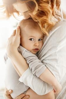 Porträt des süßen kleinen kindes, das die kamera mit interessiertem ausdruck betrachtet, während mutter zärtlich handfläche kuschelt und ihr neugeborenes baby küsst.