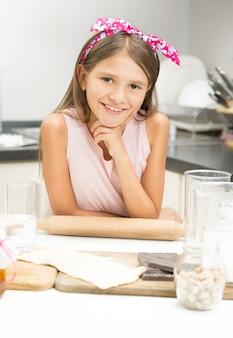 Porträt des süßen mädchens mit rosa schleife auf dem haar, das mit hölzernem nudelholz aufwirft
