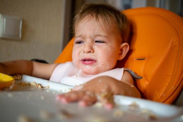 Porträt des süßen weinenden babykleinkindes, das mit esstisch sitzt
