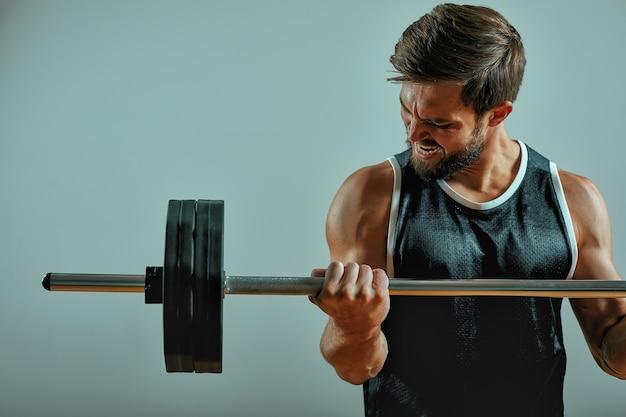 Porträt des super fit muskulösen jungen mannes, der im fitnessstudio mit langhantel auf grauem hintergrund arbeitet