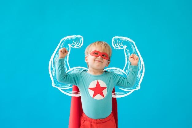 Porträt des superheldenkindes. superheldenkind gegen blaue wand.