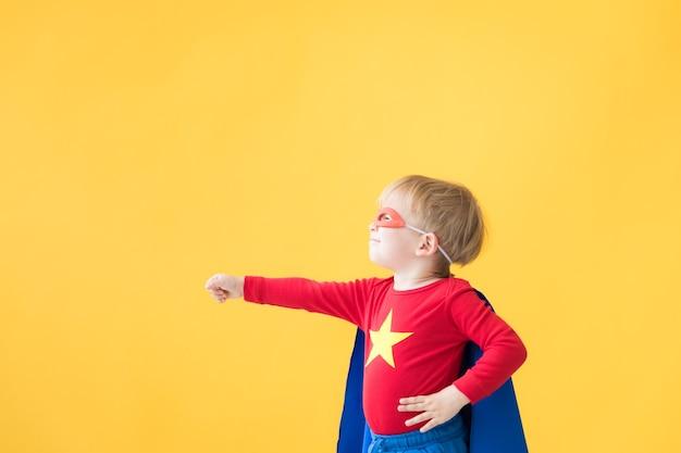Porträt des superheldenkindes. superheldenkind gegen gelben papierhintergrund. glückliches kind mit roter maske und umhang des superhelden. kindertraum und fantasiekonzept