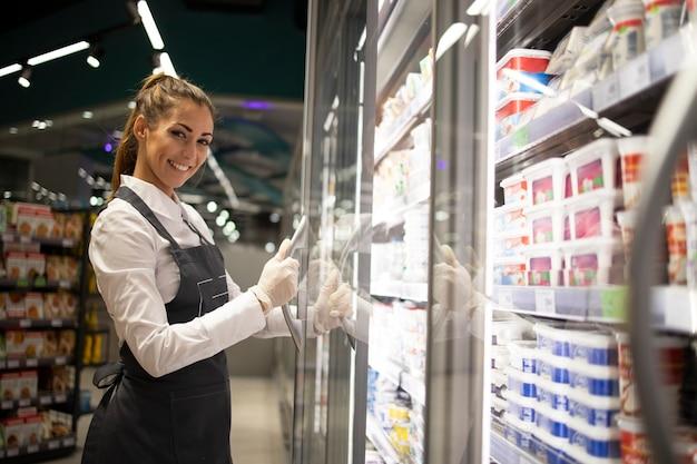 Porträt des supermarktarbeiters, der mit dem gefrierschrank mit essen steht