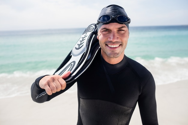 Porträt des surfers mit den flossen, die auf dem strand stehen