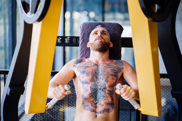 Porträt des tätowierten bärtigen mannes, der auf brustpressmaschine im fitnessstudio nahe fenster ausarbeitet