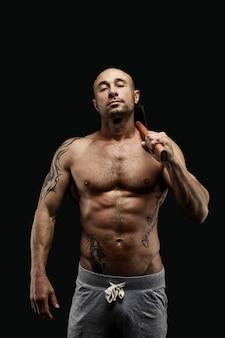 Porträt des tätowierten hemdlosen athleten mit hammer auf schulter