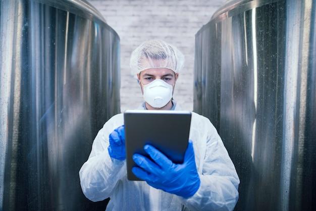 Porträt des technologen in der weißen schutzuniform, die tablette in der nahrungsmittelproduktionsfabrik hält