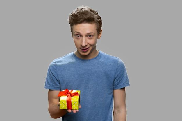 Porträt des teenagers, der geschenkbox hält. hübscher jugendlich kerl, der geschenkbox gegen grauen hintergrund anbietet.