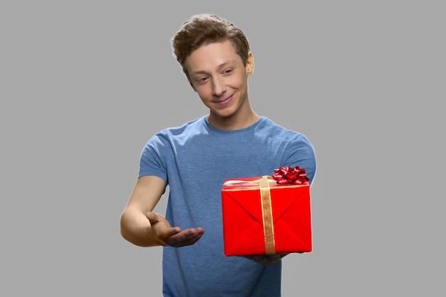 Porträt des teenagers, der geschenkbox hält. netter junge im blauen t-shirt, das geschenkbox auf grauem hintergrund anbietet. spezielles urlaubsangebot.