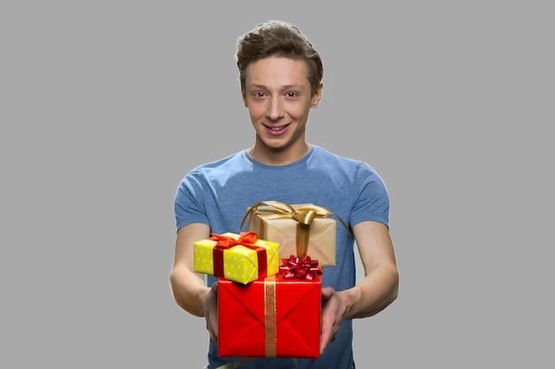 Porträt des teenagers, der geschenkboxen anbietet. hübscher jugendlich kerl, der geschenkboxen auf grauem hintergrund hält. geburtstagsgeschenkkonzept.