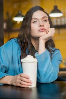Porträt des teenagers, der mit heißer schokolade aufwirft