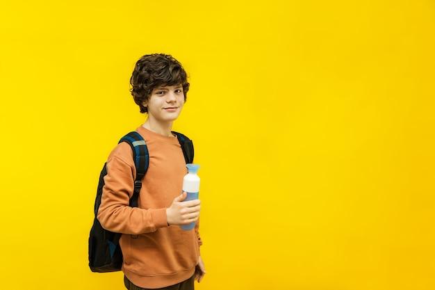 Porträt des teenagers mit rucksack, hält eine plastikflasche mit wasser in seinen händen, lokalisiert auf gelbem hintergrund