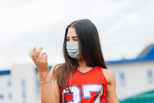 Porträt des tennisspielermädchens, das einen ball außerhalb mit schutzmasken hält